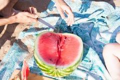 Groep die mensen een watermeloen op het strand eet stock fotografie