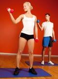 Groep die mensen gewichten in gymnastiek opheft Stock Afbeeldingen