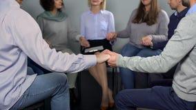 Groep die mensen handen houden tijdens therapie in rehab, psychotherapist steun stock fotografie