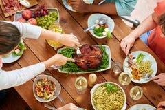 Groep die mensen kip voor diner eten stock afbeelding