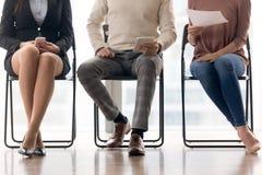 Groep die mensen op baangesprek wachten, op stoelen zitten stock afbeelding