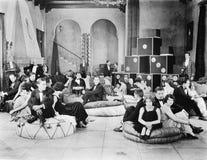 Groep die mensen op overmaatse kussens in een zaal zitten (Alle afgeschilderde personen leven niet langer en geen landgoed bestaa Royalty-vrije Stock Afbeeldingen