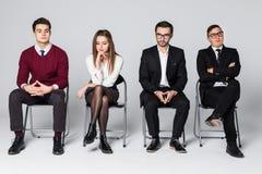 Groep die mensen op stoelen zitten die gesprekken wachten Vier mensen wachten op vergadering over witte achtergrond royalty-vrije stock foto