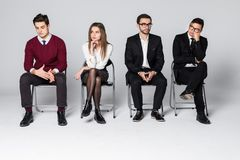 Groep die mensen op stoelen zitten die gesprekken wachten Vier mensen wachten op vergadering over witte achtergrond stock fotografie