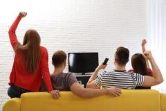Groep die mensen op TV samen op bank in woonkamer letten stock fotografie