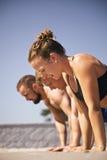 Groep die mensen opdrukoefeningen op strand doen Royalty-vrije Stock Fotografie