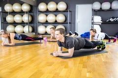 Groep die mensen plank doen bij de klasse van de geschiktheidsgymnastiek royalty-vrije stock afbeeldingen