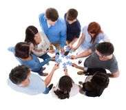 Groep die mensen raadselstukken verbinden Stock Fotografie