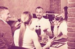 Groep die mensen uit merrily in het restaurant van het land dineren Stock Afbeeldingen