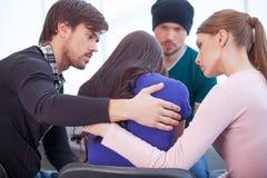 Groep die mensen verstoorde vrouw troosten. stock foto