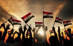 Groep die Mensen Vlag van Syrië in Achterlit golven Stock Afbeelding