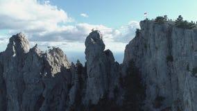 Groep die mensen zich bovenop een berg over het overzees bevinden schot Zij plantten de nationale vlag stock videobeelden