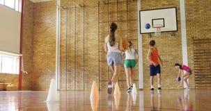 Groep die middelbare schooljonge geitjes basketbal spelen stock footage