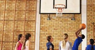 Groep die middelbare schooljonge geitjes basketbal spelen stock video