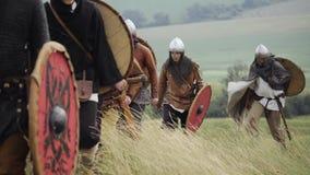 Groep die Middeleeuws Viking met schilden vooruit op de weide lopen