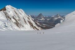Groep die mountaneers op een gletsjer in een zonnige dag lopen: in bac stock foto