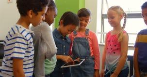 Groep die multi-etnische schooljonge geitjes digitale tablet in klaslokaal gebruiken op school 4k stock videobeelden