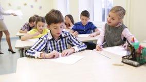 Groep die schooljonge geitjes test in klaslokaal schrijven stock video