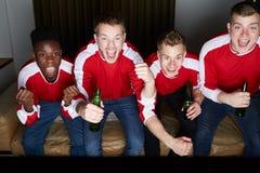Groep die Sportenventilators op Spel op TV thuis letten royalty-vrije stock foto