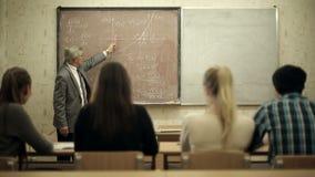 Groep die studenten in een klaslokaal, als hun leraar de luisteren houdt een lezing stock footage