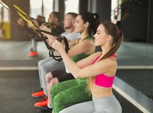 Groep die TRX-opleiding in gymnastiek uitvoeren stock afbeeldingen
