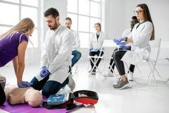 Groep dokters tijdens de eerste hulp die binnen opleiden stock foto