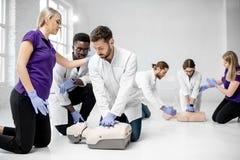 Groep dokters tijdens de eerste hulp die binnen opleiden stock fotografie