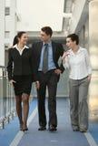 Groep drie personen die het lopen bureau spreken stock afbeelding