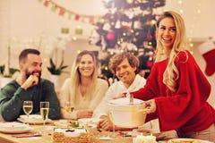 Groep familie en vrienden die Kerstmisdiner vieren stock afbeeldingen