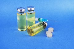 Groep flesjes met geneeskunde, tabletten en spuiten op blauwe lijst stock foto's