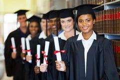 Groep gediplomeerden in bibliotheek stock afbeeldingen