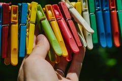 Groep gekleurde wasknijpers die een mens houdt Stock Afbeelding