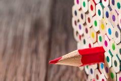 Groep gele potloden, oranje, rood, purper, wintertaling, blauw, viooltje groen, met één individueel rood potlood stock fotografie