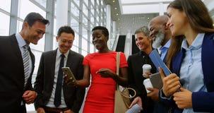 Groep gelukkige bedrijfsmensen die de mobiele telefoon 4k bekijken stock videobeelden