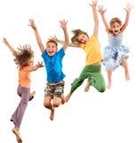 Groep gelukkige en barefeet vrolijke sportieve kinderen die springen dansen Stock Foto
