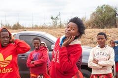 Groep gelukkige glimlachende Afrikaanse mooie jonge meisjes in heldere rode kleren in openlucht dicht omhoog stock afbeelding