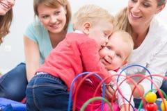Groep gelukkige jonge moeders die op hun leuk en gezond babysspel letten Royalty-vrije Stock Fotografie