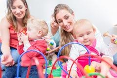 Groep gelukkige jonge moeders die op hun leuk en gezond babysspel letten stock afbeelding