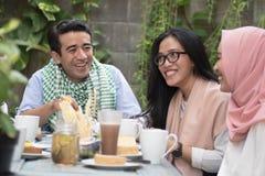 Groep gelukkige jonge moslim hebbend diner openlucht tijdens ramadan stock afbeelding
