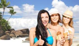 Groep gelukkige jonge vrouwen met roomijs op strand Stock Foto's