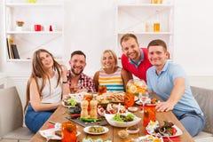 Groep gelukkige jongeren bij dinerlijst, vriendenpartij stock foto's