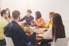 Groep gelukkige jongeren die bij dinerlijst spreken, vriendenpartij Stock Afbeelding