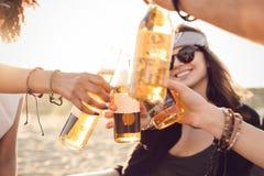 Groep gelukkige jongeren die samen bij het strand zitten Royalty-vrije Stock Foto's