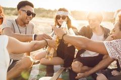 Groep gelukkige jongeren die samen bij het strand zitten Royalty-vrije Stock Fotografie