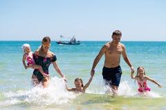 Groep gelukkige kinderen die en in het overzeese strand spelen bespatten Jonge geitjes die pret hebben in openlucht De zomervakan royalty-vrije stock fotografie