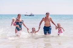 Groep gelukkige kinderen die en in het overzeese strand spelen bespatten Jonge geitjes die pret hebben in openlucht De zomervakan royalty-vrije stock foto