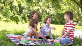 Groep gelukkige kinderen die in openlucht in de zomerpark spelen Langzame Motie stock footage