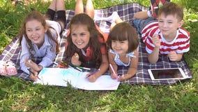 Groep gelukkige kinderen die in openlucht in de zomerpark spelen Langzame Motie stock video
