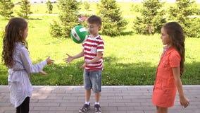 Groep gelukkige kinderen die in openlucht in de zomerpark spelen Langzame Motie stock videobeelden