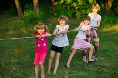 Groep gelukkige kinderen die touwtrekwedstrijd buiten op gras spelen Jonge geitjes die kabel trekken bij park royalty-vrije stock afbeelding